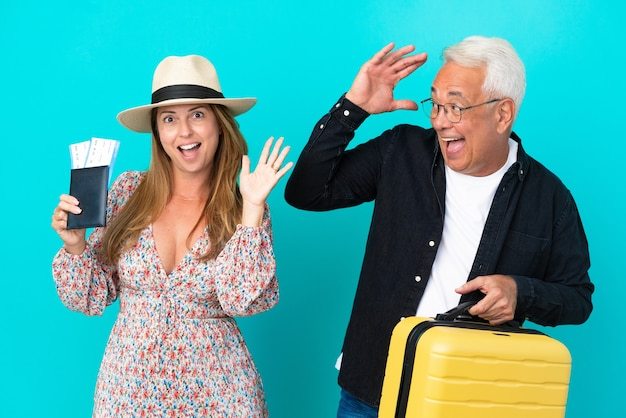 Coppia di mezza età che va a viaggiare e tiene in mano una valigia isolata su sfondo blu con espressione facciale sorpresa e scioccata