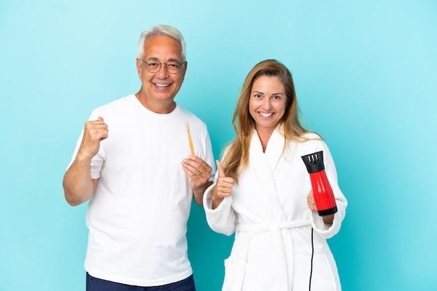 Coppia di mezza età che tiene asciugatrice e spazzolino da denti isolato su sfondo blu dando un pollice in alto gesto con entrambe le mani e sorridente