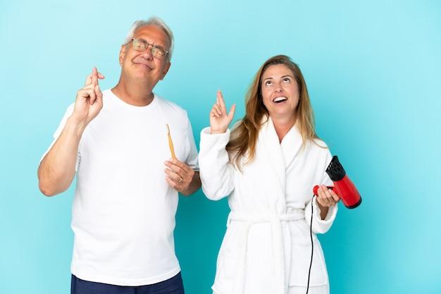 Coppia di mezza età che tiene asciugatrice e spazzolino da denti isolato su sfondo blu con le dita incrociate e augurando il meglio