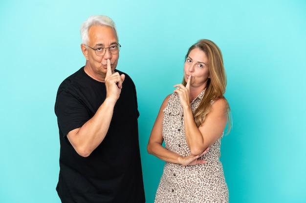 Coppia di mezza età isolata su sfondo blu che mostra un segno di chiusura della bocca e gesto di silenzio