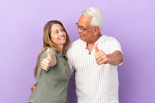 Coppia di mezza età isolata su sfondo viola che dà un gesto di pollice in alto