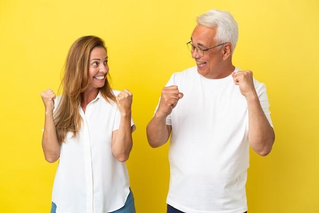 Coppia di mezza età isolata su sfondo giallo che celebra una vittoria