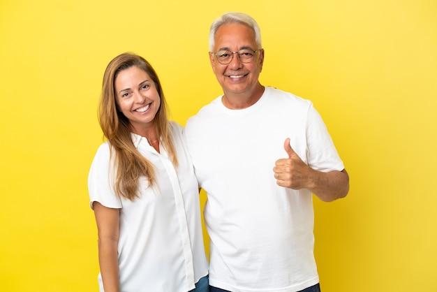Coppia di mezza età isolata su sfondo giallo che dà un gesto di pollice in alto