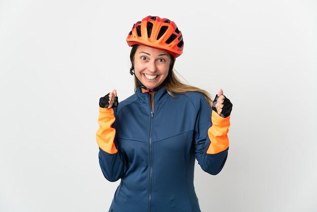 Donna ciclista di mezza età isolata su bianco che celebra una vittoria nella posizione del vincitore