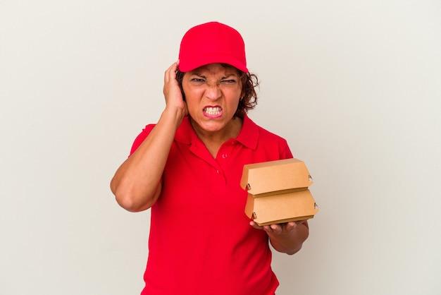 Donna di consegna di mezza età che prende hamburger isolati su sfondo bianco che copre le orecchie con le mani.