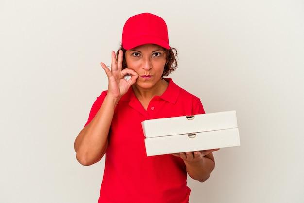 Donna di consegna di mezza età che prende le pizze isolate su fondo bianco con le dita sulle labbra mantenendo un segreto.