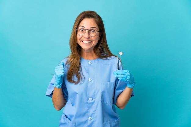 Dentista di mezza età donna brasiliana che tiene strumenti isolati
