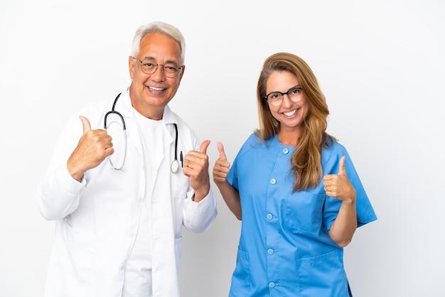 Medico e infermiere di mezza età isolati su sfondo bianco che danno un gesto di pollice in alto con entrambe le mani e sorridendo