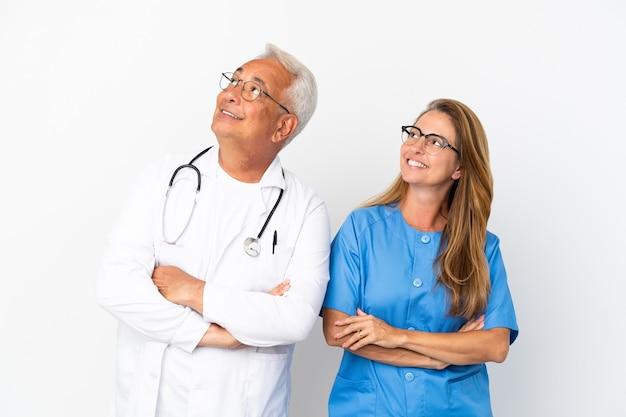 Medico e infermiere di mezza età isolati su sfondo bianco alzando lo sguardo mentre sorridono