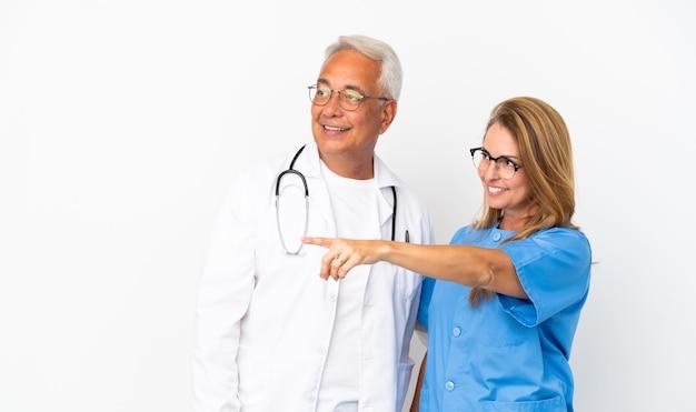 Medico e infermiere di mezza età isolati su sfondo bianco che puntano al lato per presentare un prodotto