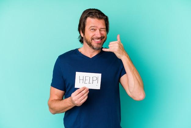 Uomo olandese di mezza età che tiene un cartello di aiuto isolato sulla parete blu che mostra un gesto di chiamata di telefono cellulare con le dita
