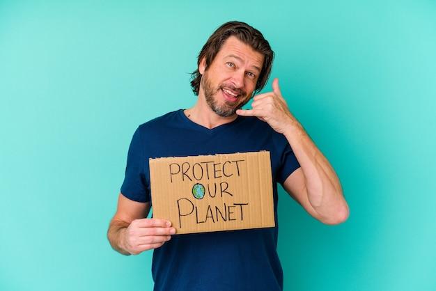 L'uomo olandese di mezza età che tiene un protegge il nostro cartello del pianeta isolato sulla parete blu che mostra un gesto di chiamata del telefono cellulare con le dita