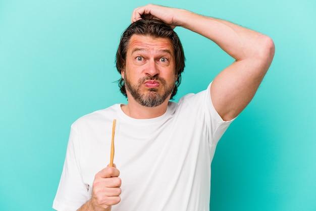 Uomo olandese di mezza età che tiene uno spazzolino da denti isolato su sfondo blu scioccato, ha ricordato un incontro importante.