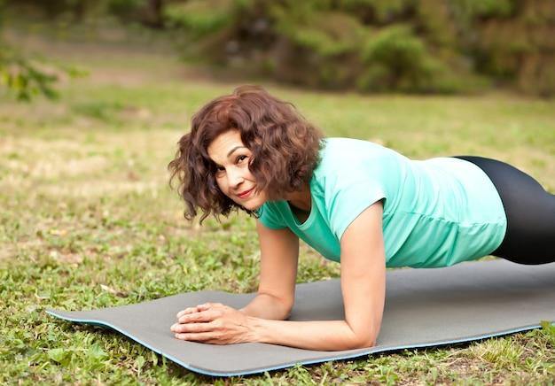 Donna anziana di mezza età che fa tavola sul materassino yoga in un parco outdoor