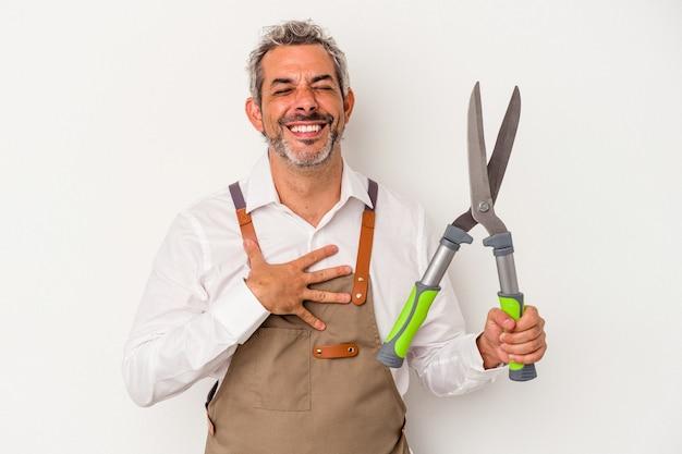 L'uomo del giardiniere di mezza età che tiene una forbice isolata su fondo bianco ride ad alta voce tenendo la mano sul petto.