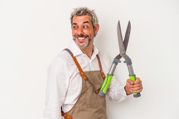 L'uomo del giardiniere di mezza età che tiene una forbice isolata su fondo bianco guarda da parte sorridente, allegro e piacevole.