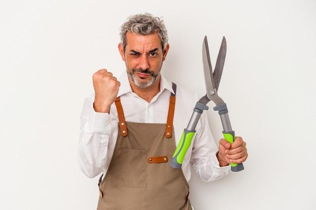 Uomo del giardiniere di mezza età che tiene le forbici isolate su fondo bianco che mostra il pugno alla macchina fotografica, espressione facciale aggressiva.