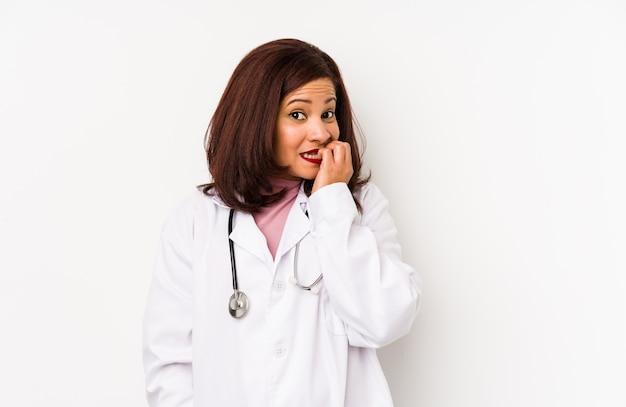 La donna latina medico di mezza età ha isolato le unghie mordaci, nervose e molto ansiose.