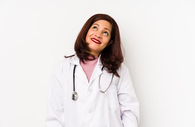 La donna di medico latino di mezza età isolata sognando di raggiungere obiettivi e scopi