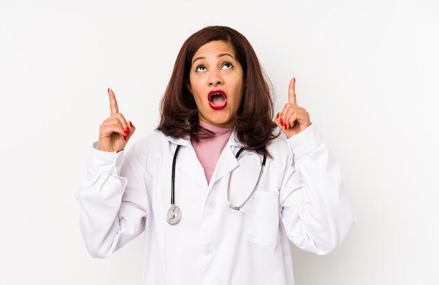 La mezza età latina medico donna isolata rivolta verso l'alto con la bocca aperta.