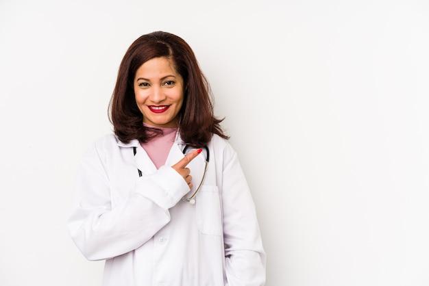La donna di medico latino di mezza età ha isolato sorridendo e indicando da parte, mostrando qualcosa nello spazio vuoto.