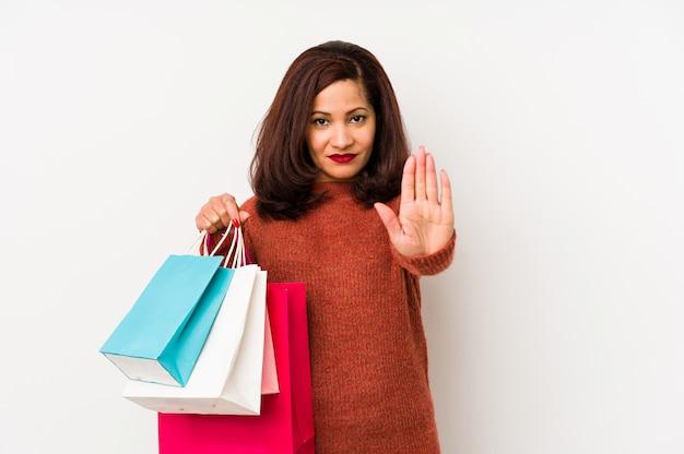 La donna latina di medio evo che tiene i sacchetti della spesa ha isolato la condizione con il fanale di arresto di rappresentazione della mano tesa, impedendovi.