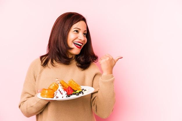 Donna latina di mezza età che tiene una cialda punti isolati con il dito pollice lontano, ridendo e spensierata.