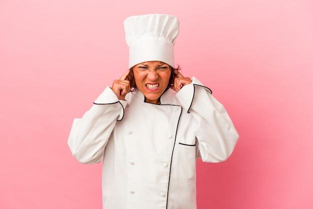 Donna latina di mezza età isolata su sfondo rosa che copre le orecchie con le mani.