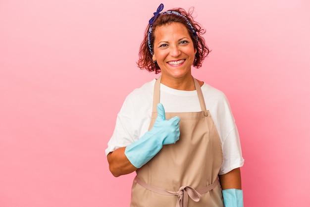 Donna latina di mezza età isolata su sfondo rosa sorridente e alzando il pollice