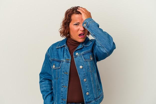 Donna latina di mezza età isolata su sfondo bianco dimenticando qualcosa, schiaffeggiando la fronte con il palmo e chiudendo gli occhi.
