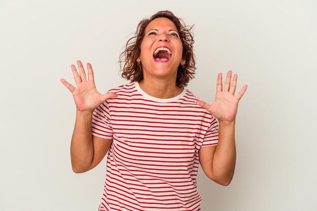 La donna latina di mezza età isolata su sfondo bianco ride ad alta voce tenendo la mano sul petto.