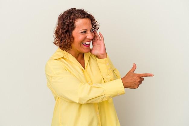 Donna latina di mezza età isolata su sfondo bianco dicendo un pettegolezzo, indicando il lato che segnala qualcosa.