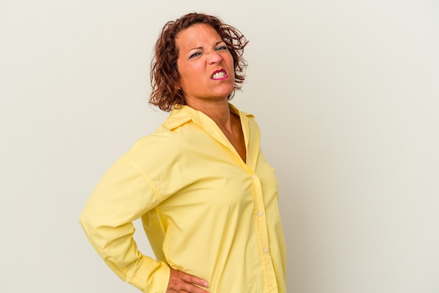 Donna latina di mezza età isolata su sfondo bianco che soffre di mal di schiena.