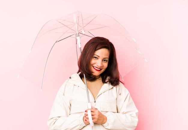 Donna latina di mezza età che indossa un ombrello isolato ridendo e divertendosi.