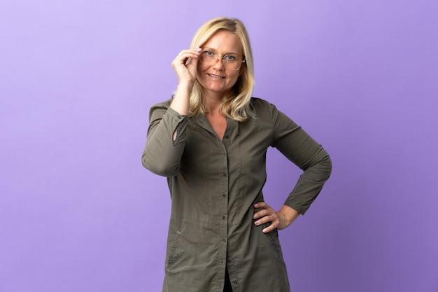 Donna lituana di mezza età isolata sulla parete viola con gli occhiali e felice