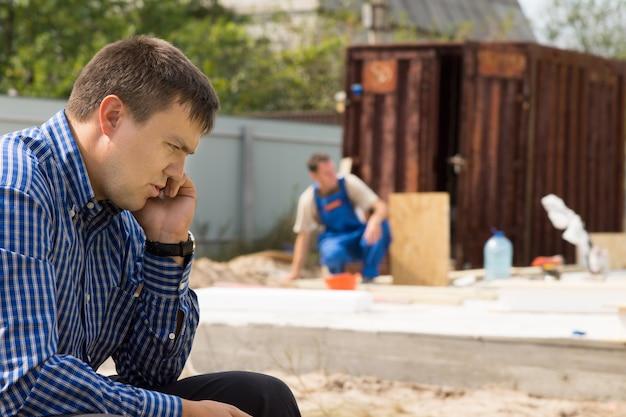 Uomo di mezza età in camicia a maniche lunghe a righe che parla seriamente con qualcuno tramite telefono.