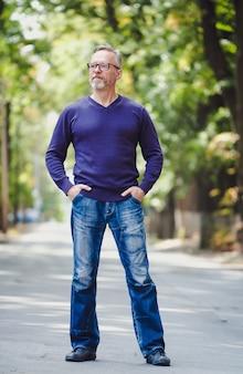 Uomo di mezza età con i capelli grigi nel parco. maglione blu. occhiali. barbuto uomo d'affari fiducioso. sfondo sfocato. mani in tasca. foto a mezzo formato