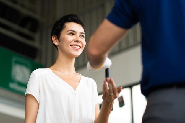 Il meccanico di mezza età con la barba dà la chiave dell'auto alla cliente femminile presso la stazione di manutenzione dell'auto e il garage di servizio automobilistico