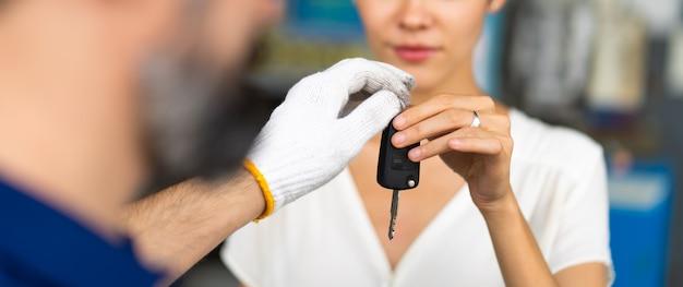 L'uomo meccanico di mezza età con la barba dà la chiave dell'auto al cliente femminile alla stazione di manutenzione dell'auto e al garage di servizio automobilistico