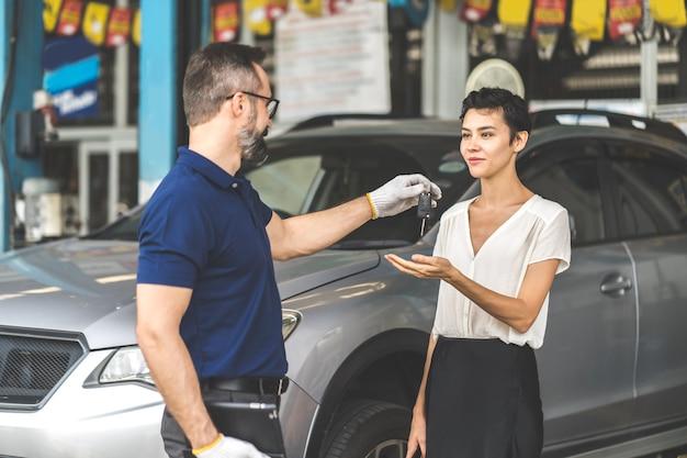 L'uomo meccanico di mezza età con la barba dà la chiave dell'auto al cliente femminile alla stazione di manutenzione dell'auto