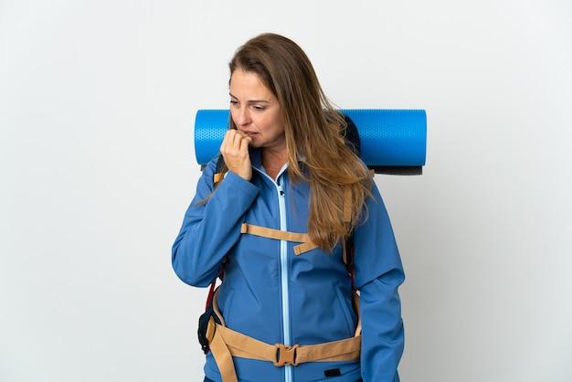 Donna alpinista di mezza età con un grande zaino sopra isolato avendo dubbi