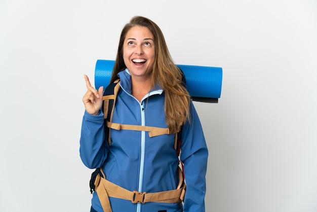 Donna alpinista di mezza età con un grande zaino sopra l'idea isolata pensando che punta il dito verso l'alto