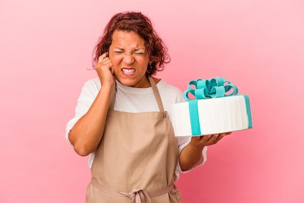 Donna latina di pasticceria di mezza età che tiene una torta isolata su sfondo rosa che copre le orecchie con le mani.