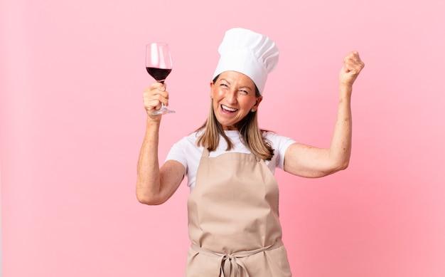 Bella donna chef di mezza età con un bicchiere di vino
