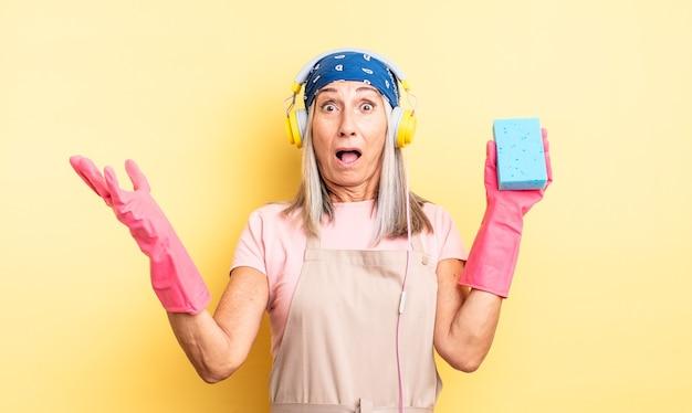 Bella donna di mezza età stupita, scioccata e stupita con un'incredibile sorpresa. detergente per pagliette