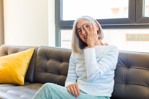Donna graziosa di mezza età che si sente annoiata, frustrata e assonnata dopo un compito noioso, noioso e noioso, tenendo la faccia con la mano
