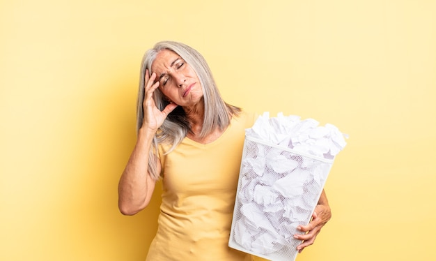 Bella donna di mezza età che si sente annoiata, frustrata e assonnata dopo una noiosa. concetto di fallimento delle palle di carta