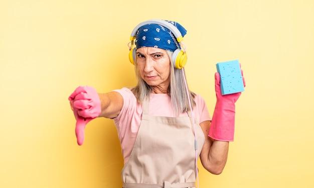 Bella donna di mezza età che si sente croce, mostra i pollici in giù. detergente per pagliette