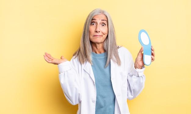 Bella donna di mezza età che si sente perplessa, confusa e dubbiosa. concetto di podologo