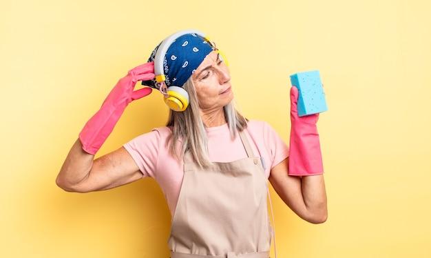 Bella donna di mezza età che si sente perplessa e confusa, grattandosi la testa. detergente per pagliette